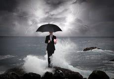 Hombre de negocios debajo de un paraguas en el mar Foto de archivo libre de regalías