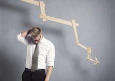 Hombre de negocios decepcionado delante del gráfico que señala abajo. Imagen de archivo