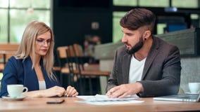 Hombre de negocios decepcionado que gesticula regañando airadamente hablar con la mujer que señala el documento del error almacen de video