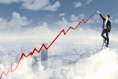 Hombre de negocios del éxito que dibuja un gráfico positivo imagen de archivo libre de regalías