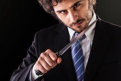 Hombre de negocios del asesinato con el cuchillo de cocina Imagen de archivo libre de regalías