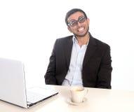 Hombre de negocios del empollón en el funcionamiento de vidrios divertido con el ordenador Imágenes de archivo libres de regalías