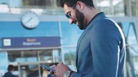 Hombre de negocios del este barbudo hermoso que hace una pausa la entrada del aeropuerto, usando su teléfono y sonrisas al mensaj almacen de video