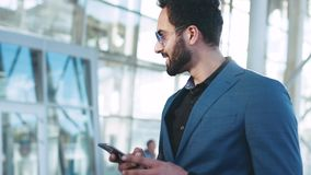 Hombre de negocios del este barbudo hermoso que hace una pausa la entrada del aeropuerto, usando su teléfono y sonrisas feliz a r almacen de metraje de vídeo