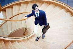 Hombre de negocios del este On Spiral Stairs Imagen de archivo