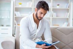 Hombre de negocios del estudiante del hombre joven que lee un libro que estudia el trabajo en Foto de archivo libre de regalías