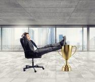 Hombre de negocios del ganador que se relaja sobre una taza de oro foto de archivo libre de regalías