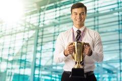 Hombre de negocios del ganador que sostiene el trofeo de oro foto de archivo libre de regalías