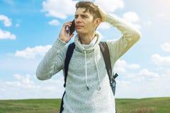 Hombre de negocios del hombre joven que habla en el teléfono móvil afuera en un campo de hierba Fotografía de archivo