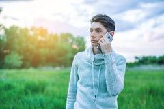 Hombre de negocios del hombre joven que habla en el teléfono móvil afuera en un campo de hierba Fotos de archivo libres de regalías
