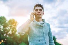 Hombre de negocios del hombre joven que habla en el teléfono móvil afuera en un campo de hierba Foto de archivo libre de regalías