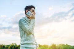 Hombre de negocios del hombre joven que habla en el teléfono móvil afuera en un campo de hierba Fotografía de archivo libre de regalías