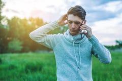 Hombre de negocios del hombre joven que habla en el teléfono móvil afuera en un campo de hierba Imagen de archivo
