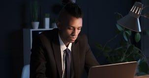 Hombre de negocios del trabajoadicto que trabaja en el ordenador portátil de la oficina en la noche