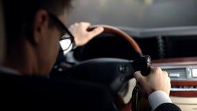 Hombre de negocios del trastorno que se sienta en coche con la botella de vino, conducción irresponsable, crisis fotografía de archivo