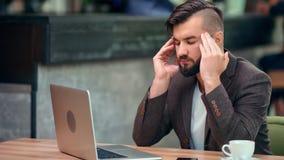 Hombre de negocios del trastorno que tiene dolor de cabeza que da masajes al templo durante el trabajo usando el ordenador portát almacen de metraje de vídeo