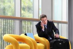 Hombre de negocios del viaje que habla en el teléfono, sentándose con equipaje, sala de espera, silla amarilla imagen de archivo