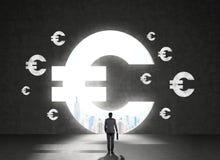 Hombre de negocios delante de símbolos euro Imágenes de archivo libres de regalías