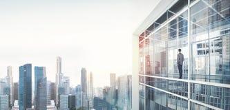 Hombre de negocios dentro del rascacielos, lookng en la ciudad imagen de archivo libre de regalías