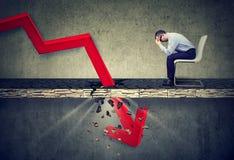 Hombre de negocios deprimido que mira abajo la flecha roja que cae que pasa a través de un piso concreto Imagen de archivo libre de regalías