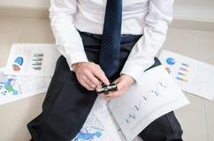 Hombre de negocios desalientador que se sienta en el piso Imagen de archivo