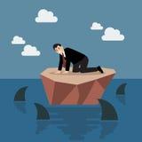 Hombre de negocios desamparado en una pequeña isla que rodeó por el tiburón Foto de archivo libre de regalías
