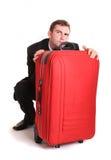 Hombre de negocios desconfiado detrás del equipaje rojo Fotografía de archivo libre de regalías