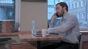 Hombre de negocios descontentado que habla en el teléfono en café metrajes