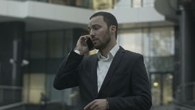Hombre de negocios descontentado que habla seriamente por el teléfono metrajes
