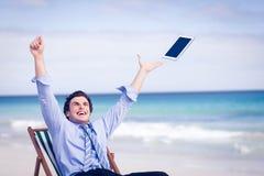 Hombre de negocios despreocupado que lanza para arriba su tableta en el aire Fotos de archivo
