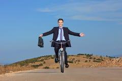 Hombre de negocios despreocupado que monta una bicicleta Imagen de archivo libre de regalías