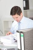 Hombre de negocios difícilmente en el trabajo que hace la investigación Fotografía de archivo