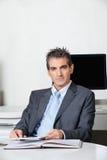Hombre de negocios With Digital Tablet que se sienta en el escritorio imagen de archivo