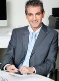 Hombre de negocios With Digital Tablet que se sienta en el escritorio imagenes de archivo