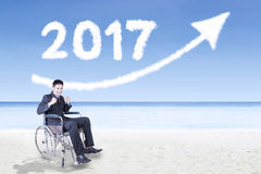 Hombre de negocios discapacitado con el número 2017 y la flecha Fotos de archivo