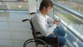 Hombre de negocios discapacitado en una silla de ruedas en un smartphone de las aplicaciones de la ventana almacen de metraje de vídeo