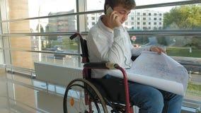 Hombre de negocios discapacitado en una silla de ruedas en un smartphone de las aplicaciones de la ventana metrajes