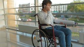 Hombre de negocios discapacitado en una silla de ruedas en un smartphone de las aplicaciones de la ventana almacen de video