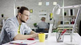 Hombre de negocios disciplinado productivo que inclina el trabajo de oficina detrás de acabado en el ordenador portátil, encargad almacen de video