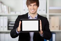 Hombre de negocios Displaying Digital Tablet en oficina foto de archivo