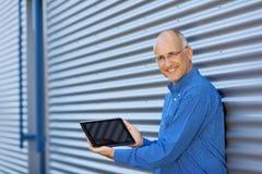 Hombre de negocios Displaying Digital Tablet mientras que se inclina en el obturador fotografía de archivo