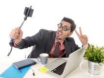 Hombre de negocios divertido del empollón en el escritorio de oficina que toma la foto del selfie con la cámara y el palillo del  Fotografía de archivo libre de regalías