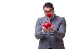 Hombre de negocios divertido del payaso con una hucha aislada en la parte posterior del blanco Fotos de archivo libres de regalías