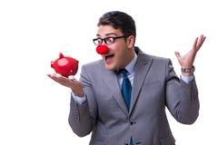 Hombre de negocios divertido del payaso con una hucha aislada en la parte posterior del blanco Foto de archivo libre de regalías