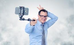 Hombre de negocios divertido en los vidrios que hacen el selfie con un palillo fotos de archivo libres de regalías