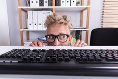 Hombre de negocios divertido Hiding Behind Desk foto de archivo