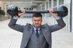 Hombre de negocios divertido que levanta pesos pesados foto de archivo libre de regalías