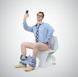 Hombre de negocios divertido que se fotografía en el retrete imagenes de archivo