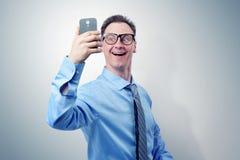 Hombre de negocios divertido que se fotografía en un smartphone fotos de archivo libres de regalías