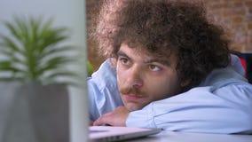 Hombre de negocios divertido soñoliento con el pelo rizado que dormita en el trabajo, durmiendo en el lugar de trabajo en oficina almacen de video